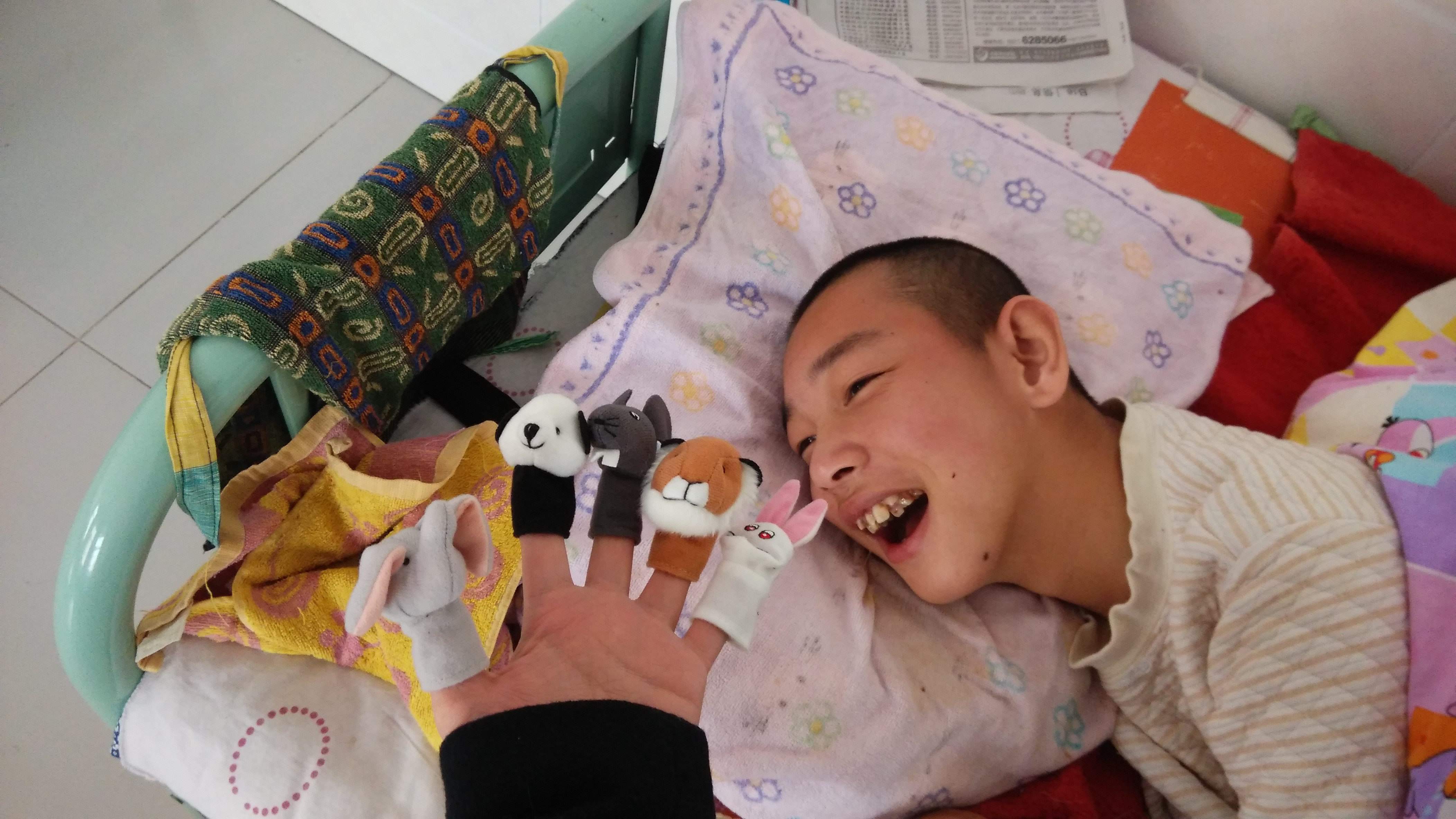 Gui laughs and smiles during story time, especially when the finger puppets are active!